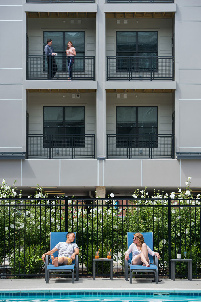 2 friends relaxing in lounge chairs by the pool atapartment in wilmington de