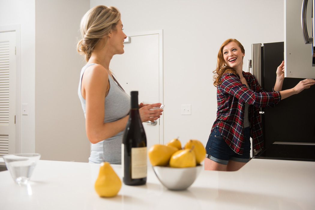 two friends enjoying wine in the kitchen of their apartment in wilmington de