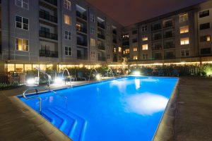 Swimming pool at Harlan Flats apartments lit up at night
